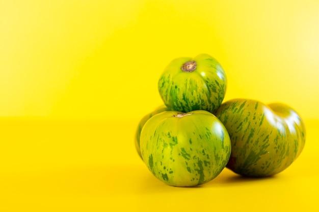 Vista di bei pomodori zebra verdi su giallo