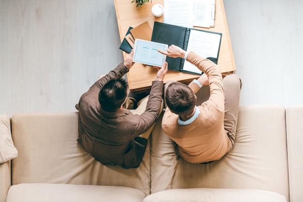 Vista di due giovani designer seduti su un morbido divano dal posto di lavoro e discutendo alcune idee creative del nuovo software alla riunione