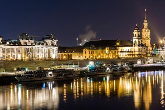 Vista di paesaggio urbano di notte dei monumenti storici con le riflessioni nel fiume elba nel centro di dresda (germania).