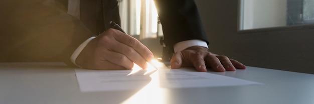 Vista di panorama dell'uomo d'affari in un contratto di firma dell'ufficio oscuro