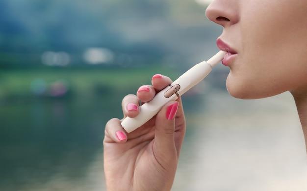 Vista di profilo del fronte della femmina adulta che fuma sigaretta elettronica all'aperto