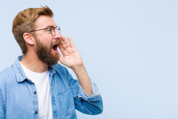 Vista di profilo del giovane uomo adulto biondo, che sembra felice ed eccitata, che grida e che chiama al copyspace dal lato