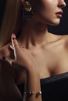 Vista di profilo del viso della ragazza che indossa set di gioielli d'oro - braccialetto di perle d'oro e anelli d'oro