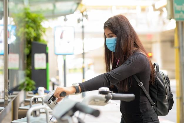 Vista di profilo della giovane donna indiana con maschera in sella a bici presso la stazione di servizio di biciclette pubbliche
