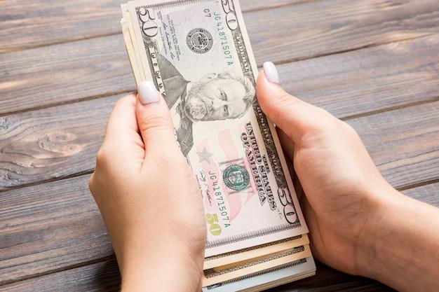 Vista di prospettiva della mano femminile che dà cento banconote in dollari. concetto di carità e donazione con spazio di copia