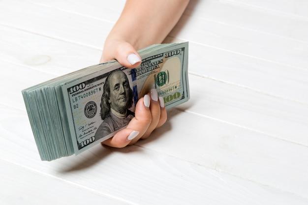 Vista di prospettiva della mano femminile che dà cento banconote in dollari su di legno. concetto di carità e donazione con spazio di copia