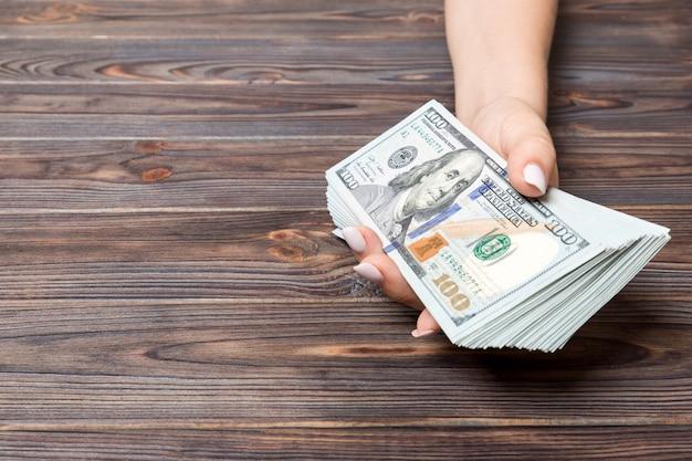 Vista di prospettiva della mano femminile che dà cento banconote in dollari su fondo di legno. concetto di carità e donazione con spazio di copia
