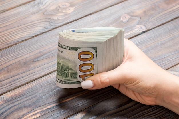 Vista di prospettiva della mano femminile che tiene un pacco di soldi su fondo di legno