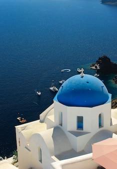 Vista di santorini della grecia con la chiesa blu della cupola.