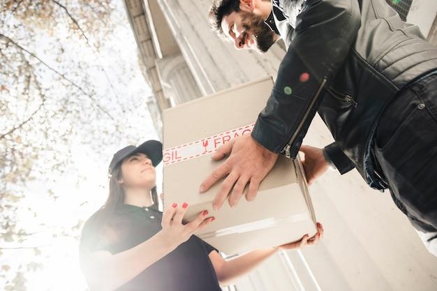 Vista di sezione bassa dell'uomo felice che riceve pacco dal corriere femminile