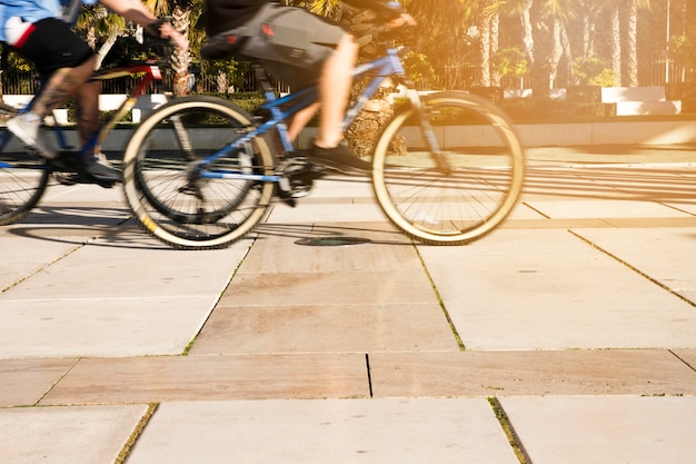Vista di sezione bassa della gente che guida bicicletta in città