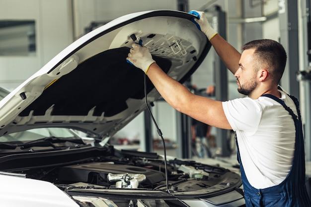 Vista di sollevamento maschio meccanica del cappuccio dell'automobile