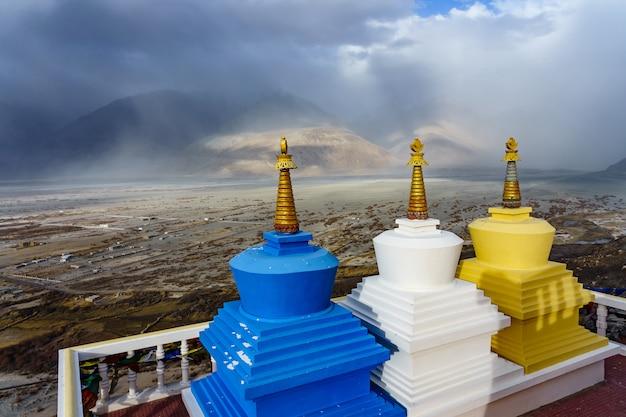 Vista di tre stupa con la valle di nubra sullo sfondo dal monastero di diskit in ladakh, in india.