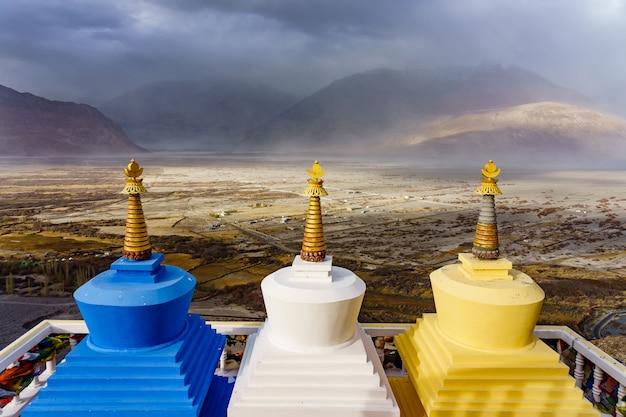 Vista di tre stupa con la valle di nubra sullo sfondo in ladakh, in india.