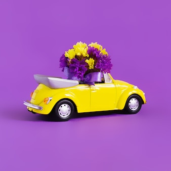Vista di un'automobile convertibile gialla variopinta con un mazzo di fiori su un rosa che lascia la nuvola blu sotto forma di cuore. concetto di vacanza, consegna, arte, trasporto
