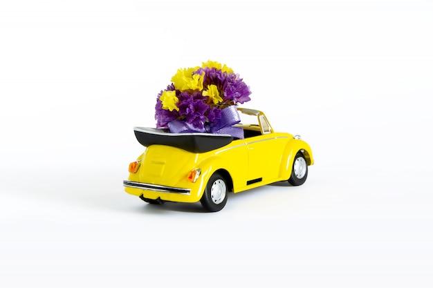 Vista di un colorato bouquet di fiori viola che si trova in una piccola auto retrò gialla. messa a fuoco selettiva. il concetto di vacanza, matrimonio, consegna di fiori, regalo