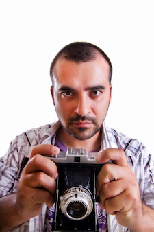 Vista di un giovane con una macchina fotografica d'epoca retrò isolata su uno sfondo bianco.