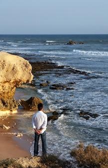 Vista di un giovane uomo con le braccia spalancate sul bordo di una scogliera.