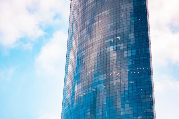 Vista di un grattacielo di vetro contemporaneo sullo sfondo del cielo nuvoloso