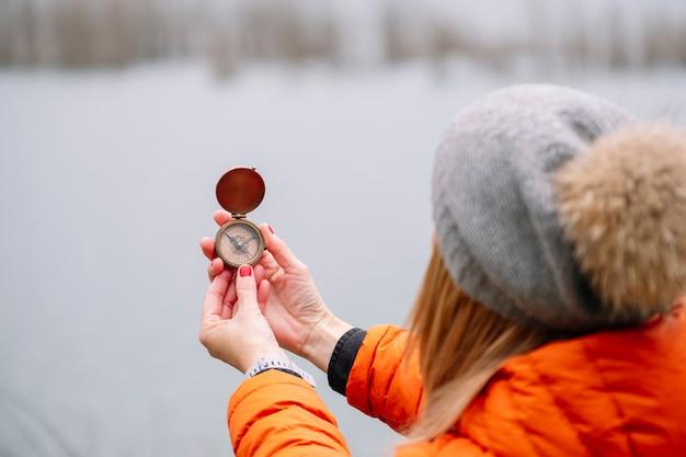 Vista di un turista in un cappello di lana e cappotto arancione in natura con una bussola su un lago di montagna