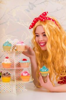 Vista di una bella ragazza bionda pinup con cupcakes colorati su un tavolo.