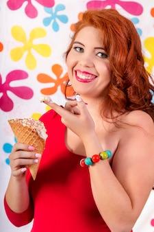 Vista di una bella ragazza rossa indossando abiti colorati in possesso di un gelato.
