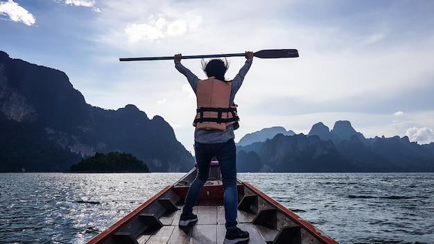 Vista di una donna alza una pagaia sulla parte anteriore della barca.