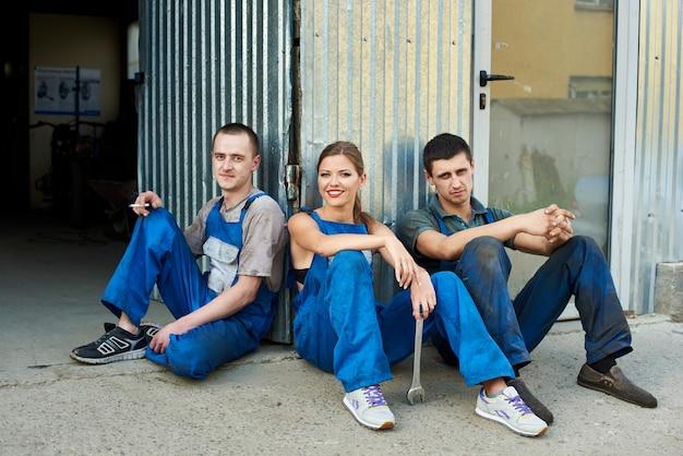 Vista di una squadra di meccanici seduti vicino al garage di riparazione. la ragazza tiene in mano una chiave inglese, seduta tra due ragazzi