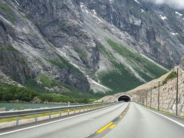 Vista di una strada asfaltata vuota con doppie linee gialle e un tunnel in montagna in riva al lago. strada di montagna norvegese con tempo nuvoloso