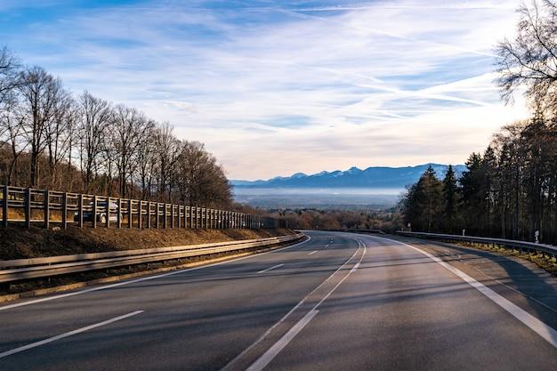 Vista di una strada curva in europa con distanti catene montuose sullo sfondo