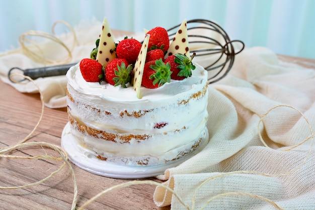 Vista di una torta nuda con fragole e pezzi di cioccolato su topping, dolce dessert