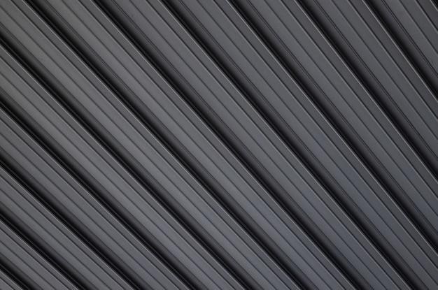 Vista diagonale alla superficie di costruzione in rilievo di metallo grigio a sfondo.