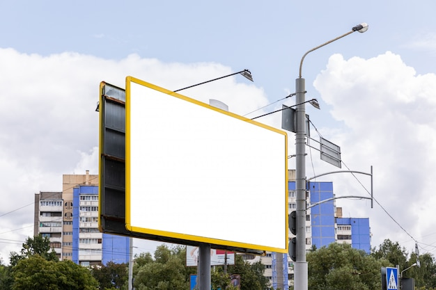 Vista diagonale del tabellone per le affissioni vuoto enorme con copyspace davanti al paesaggio della costruzione