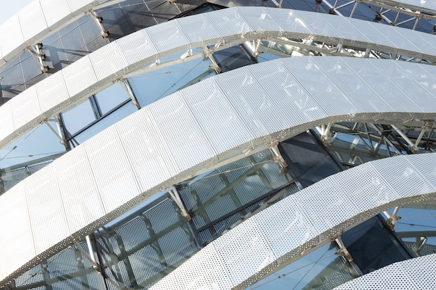 Vista diagonale dell'alta edilizia moderna con pannello forato in metallo con fori rotondi e finestre. angolo di un edificio moderno