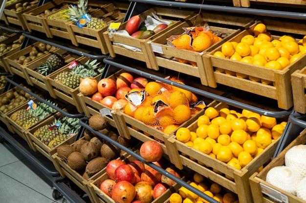 Vista diagonale delle scatole di legno dell'aletta con frutta esotica sul contatore in supermercato