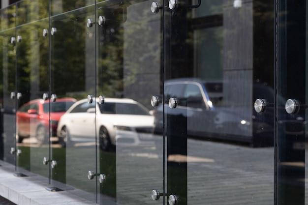 Vista diagonale di finestre di vetro o parete con elementi rotondi in acciaio con automobili e alberi di riflessione su di esso.
