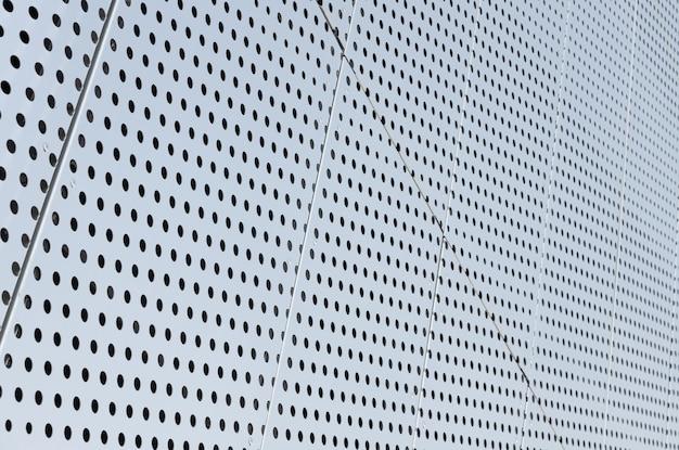 Vista diagonale di griglie metalliche e fori rotondi nella superficie metallica, pannelli forati per.