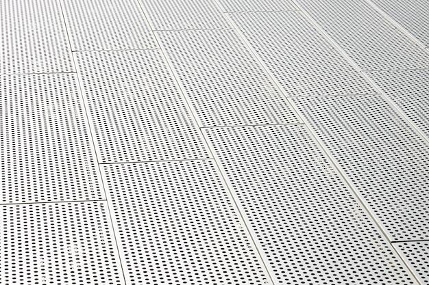 Vista diagonale di griglie metalliche e fori rotondi nella superficie metallica, pannelli forati