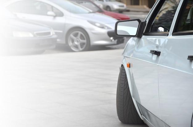 Vista diagonale di una macchina bianca lucida che si erge su un quadrato di piastrelle grigie
