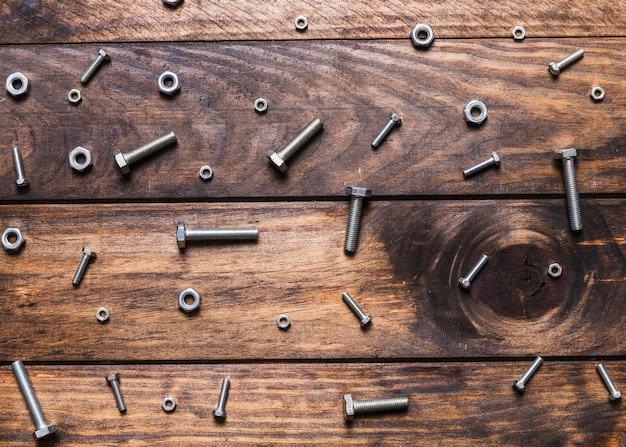 Vista elevata dei bulloni e dei dadi su fondo di legno
