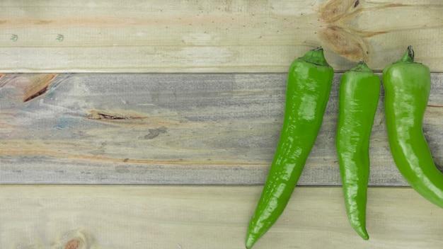 Vista elevata dei peperoncini verdi sul contesto di legno