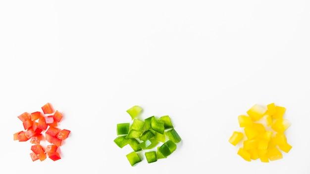 Vista elevata dei peperoni dolci tagliati variopinti sul contesto bianco