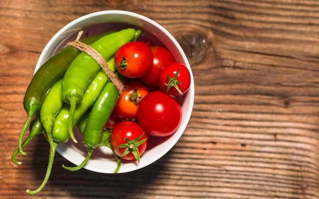 Vista elevata dei pomodori ciliegia e dei peperoncini verdi su superficie di legno