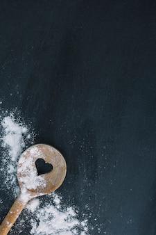 Vista elevata del cucchiaio e della farina di forma del cuore sulla superficie del nero