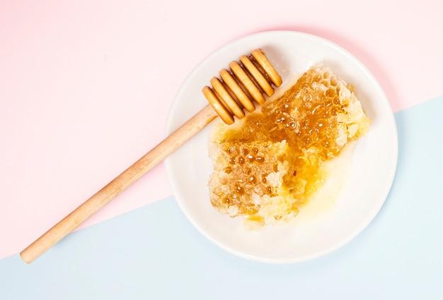 Vista elevata del favo e mestolo di legno del miele in zolla bianca