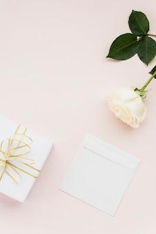 Vista elevata del fiore bianco; regalo e busta su sfondo colorato