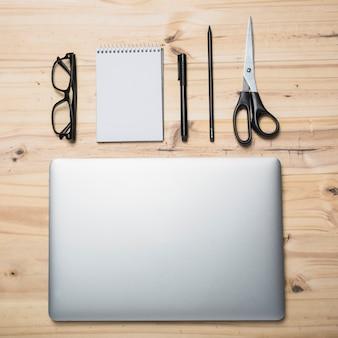 Vista elevata del laptop; cartolerie e spettacoli su fondo in legno