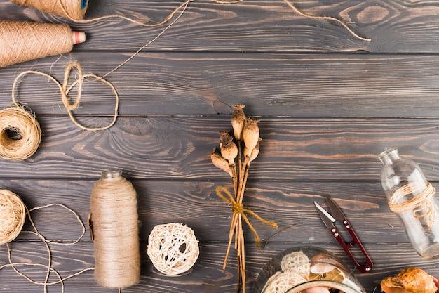 Vista elevata del materiale artigianale con baccelli di papavero e bottiglia di vetro