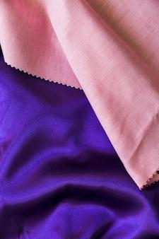 Vista elevata del materiale del tessuto rosa e viola