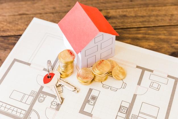 Vista elevata del modello della casa con le monete chiave e impilate sopra la cianografia